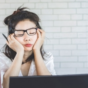 Woman in front of computer looking tired and not getting work done.